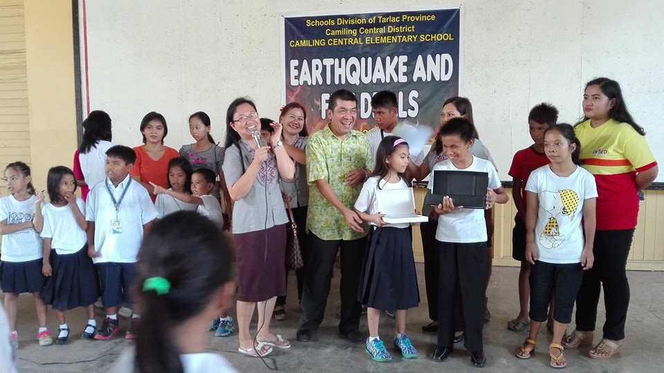 Photo of Tony Llanes of Team ATRIEV with visually-impaired students Christian Mark Agbuya and Choleen Siquete. The students are holding the computers donated by Peter Ngo of Manila Downtown's Y'S Men'S Club. With them are other students and teachers of Camiling Central School. (photo by Jane Tangonan)