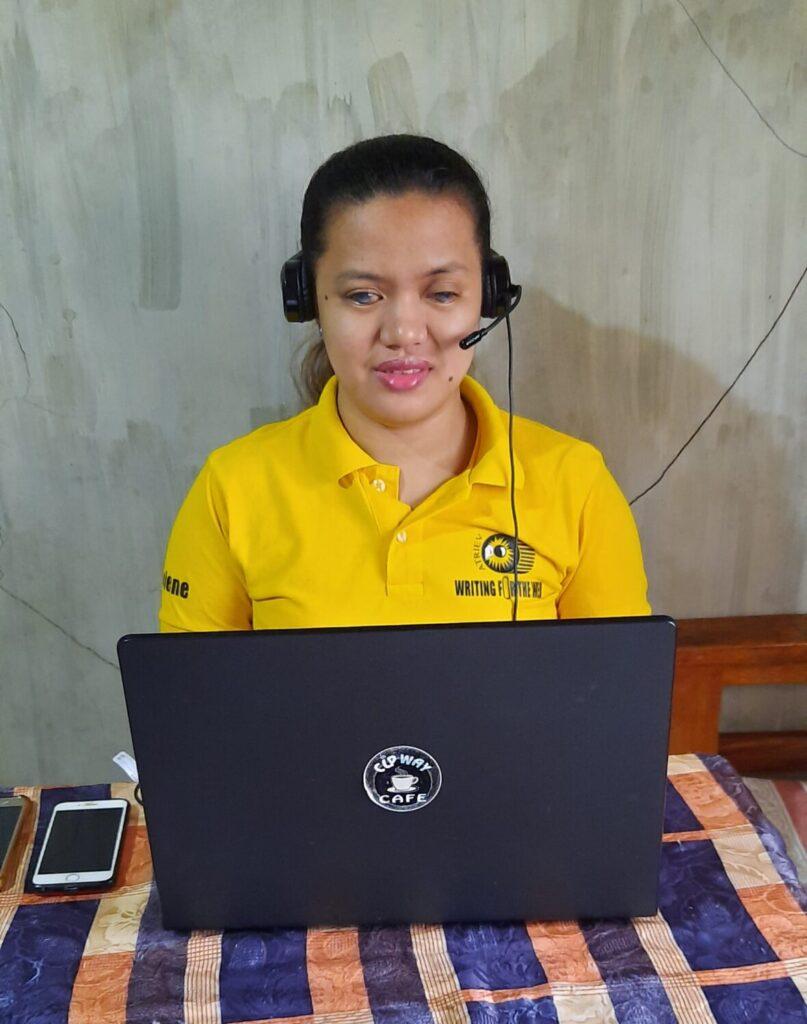 Jaelene sitting in front of her laptop wearing headphones